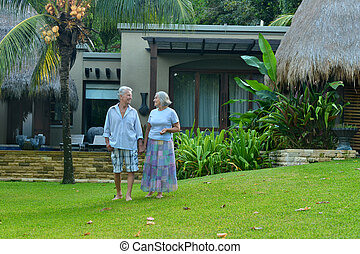 elderly couple standing embracing outdoors - Portrait of a...