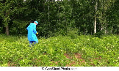 man spray potato vermin - man with blue protecting coat...