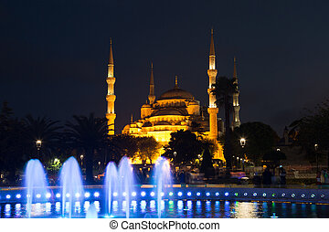 fountain with blue illumination on Sultanahmet square in front of the Blue mosque (Sultan Ahmed Mosque)in Istanbul in the evening