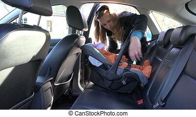 woman fasten baby seat - blond mother fasten baby safety...