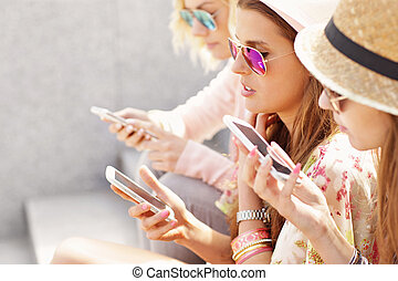 Group of friends using smartphones in the city