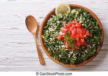 Tabbouleh salad in a wooden bowl Horizontal top view -...