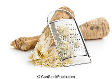 grated horseradish root on white background