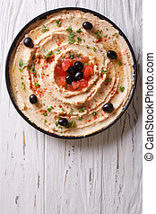 Fresh hummus with olives and tomatoes. vertical top view -...