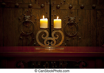 Candles burning on table in front of old rustic door -...
