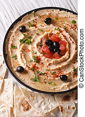 hummus with olives and herbs on a plate close-up Vertical -...
