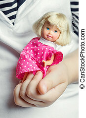 Baby doll - ?hild's hand holding small baby doll