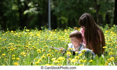 Young mother and her daughter read a childrens book outdoors