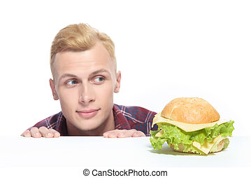 Close up of young man looking at sandwich