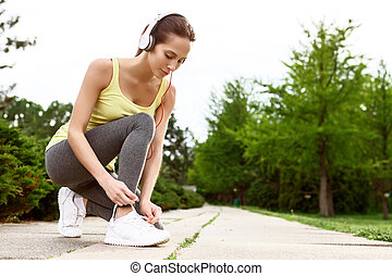 Woman lacing her shoes in park