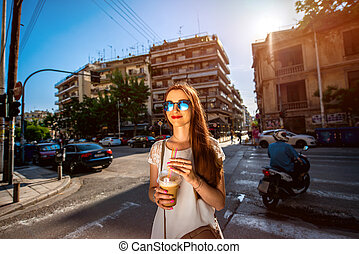 Woman walking on the street with take away coffee - Young...
