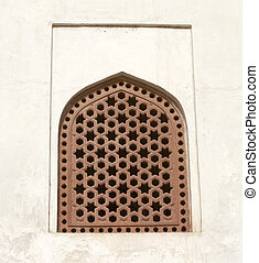 Old window with a lattice on a white wall