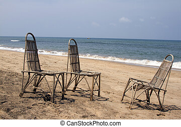 Three wattled chairs stand on a beach, wait for people...
