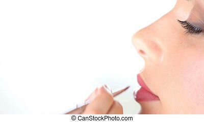 makeup artist applying lipstick on model lips with brush -...