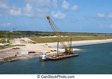 Dredging shore line and adding stone barrier wall using a...