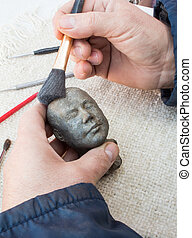 Hands of sculptor hold sculpture and clean it with brush.