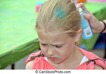 girl getting hair spry painted - Young Caucasian girl...