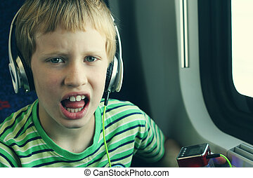Portrait of cute boy with headphones traveling in the train