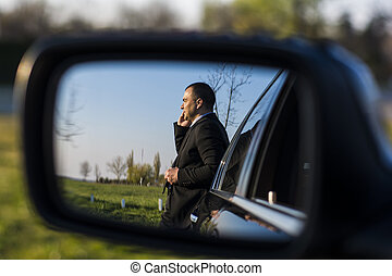 Business man on the phone in rearview mirror
