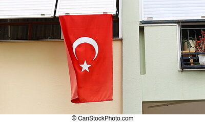 Turkish flag in front of a house balcony