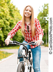 Blond lady with her bike - : Portrait of a young beautiful...
