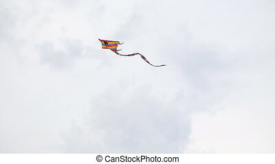 Multicolored kite soars in the sky with clouds -...