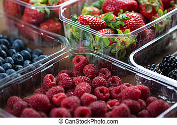 Farm fresh berries fruit in plastic trays on wodden table