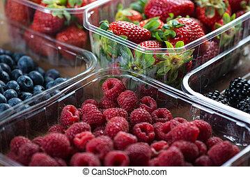 Farm fresh berries fruit in plastic trays on wodden table