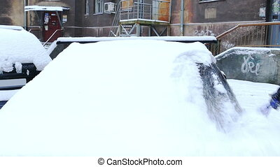 Man Removing Snow From Car Windshield in a Snowy Winter Morning