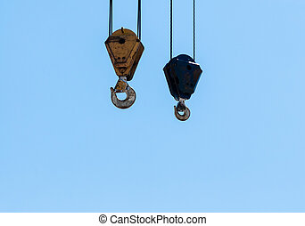 Pair of hanging industrial crane hoists on pale blue sky.