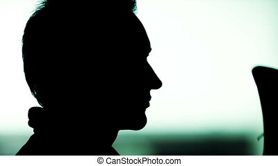 Black silhouette of man profile putting hat on