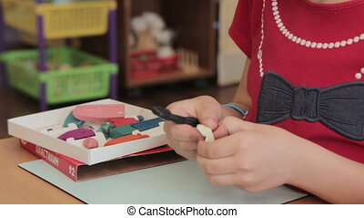 Child moulds from plasticine on table, HD