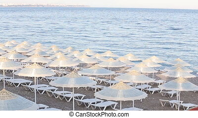 Many straw beach umbrellas at the seashore in Turkey - Many...