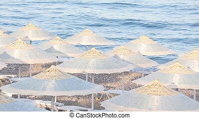 Many straw beach umbrellas at the seashore in Turkey