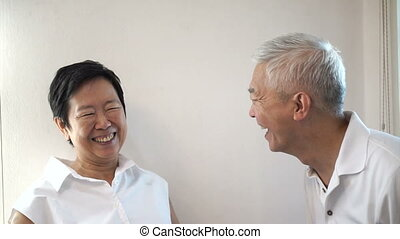 Happy Asian senior couple on white background. Laughing and...