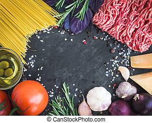 Spaghetti Bolognese ingredients on a dark stone background with a copy space in the center