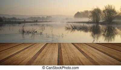 Landscape of lake in mist with sun glow at sunrise with...