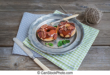Cinnamon donuts with caramel icing and pekans served with...