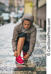 Woman runner kneeling down to tie running shoe in rain - A...