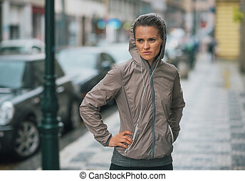Woman runner wearing rain gear stopped and feeling...