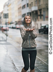 Athletic, happy woman holding her hands out to catch rain...