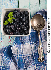Pot with fresh blueberries mint leaf and silver spoon