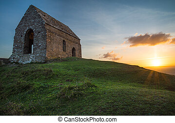Romantic sunset on Cornish coast with lonelly chapel on...