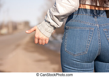 girl hitchhiking on the street - women is hailing a car on a...