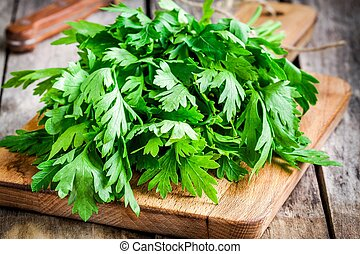 organic fresh bunch of parsley closeup on wooden cutting...