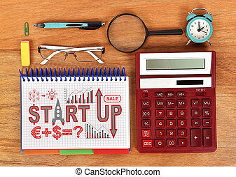 start up diagram in notebook and red calculator