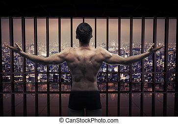 Conceptual picture of muscular guy looking at the city panorama