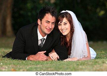 Wedding Couple Outdoors - Beautiful wedding couple laying...