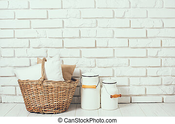 basket with a pillow and milk cans - Wicker basket with a...