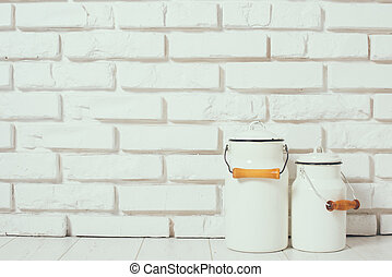 Milk cans at the white brick wall on the floor, rustic home...